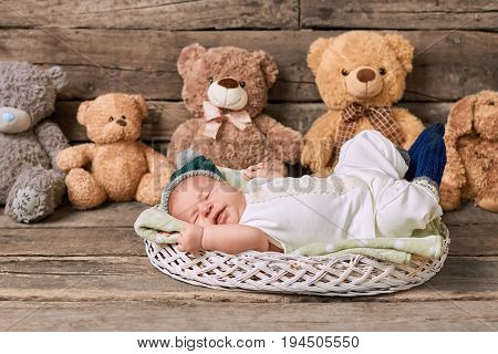 Basket, kid and teddybears. Infant with eyes closed.