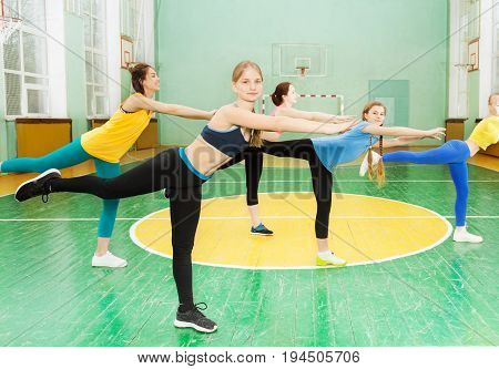 Group of teenage girls standing on one leg in the pose of swallow in gymnasium