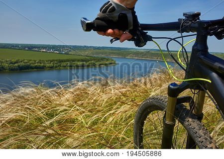 Close-up of the cyclist holding bicycle on the meadow in the countryside against beautiful landscape. Detail of the mountainbike. Sportsman dressed in the sportwear. Beautiful sky and river like a background. Concept of the healthy lifestyle.