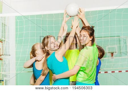 Portrait of teenage girls and boys playing volleyball in school gymnasium