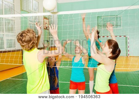 Teenagers playing volleyball, striking and serving the ball in school gymnasium