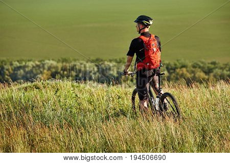 Rear view of the sportsman with his mountain bike stands on the meadow and looking away in the countryside. Young cyclist dressed in the sportwear, with helmet and backpack. Beautiful landscape like a background. Concept of the helathy lifestyle.
