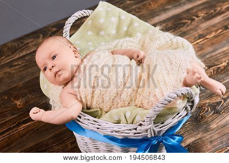 Baby in basket with bow. Infant boy wrapped in blanket. The gift of new life.