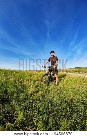 Young cyclist cycling on the green meadow against beautiful blue sky with clouds in the countryside. Attractive sportsman dressed in the black sportwear, helmet and with red backpack. Concept of the healthy lifestyle.
