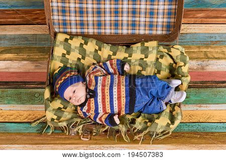 Small child in knitted sweater. Suitcase with baby, wooden background. Trendy clothes for infants.