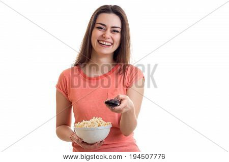 Cheerful brunette woman watching tv with pop-corn isolated on white background