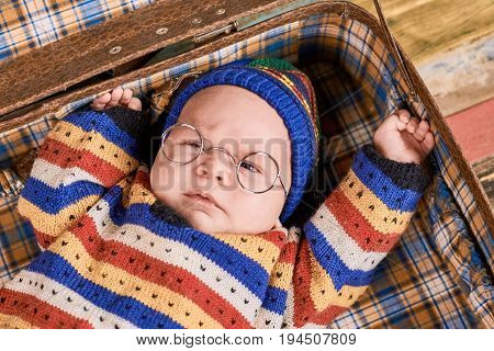 Baby in spectacles. Child in suitcase close up. The future scholar.