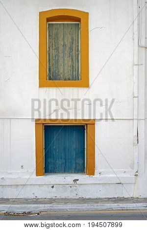 abandoned wooden house with boarded up two colourful windows