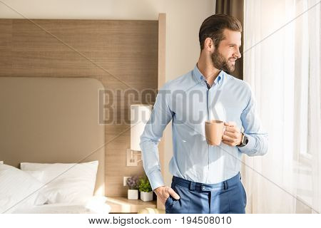 Young male business traveler hotel accomodation drinking coffee