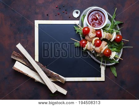 Raw shish kebabs with vegetables and greens near a coated board on a concrete background, flat lay copy space