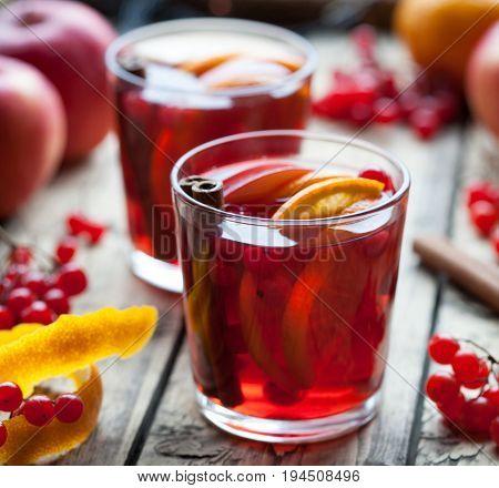Homemade refreshing cold sangria lemonade or aperol with orange, berries, cinnamon, anise on wooden table. Close up summer vitamin antioxidant beverage.
