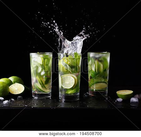 Mojito traditional beach refreshing cocktail alcohol drink in glass with splash, bar preparation soda water, lime, mint leaves, sugar, and rum. Dark black background. Square format frame