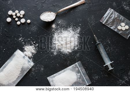 Set Of Different Drugs - Powder And Pills And A Syringe On A Black Background