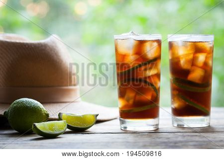 Cuba Libre or long island iced tea cocktail with lime, cola, ice, mint and rum on wooden table with a straw hat and view to the terrace. Close up summer beverage. Cold longdrink or lemonade