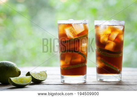 Two glasses Cuba Libre cocktail with lime, ice and mint on wooden table with view to the terrace. Close up summer beverage. Copy space for text. Cold longdrink or lemonade.