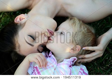 Smiling cute baby boy small little son and pretty mother woman lying on green grass on sunny summer nature outdoors on natural background. Happy mothers day family love