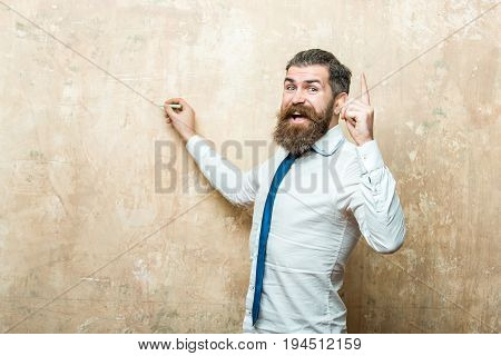 businessman or hipster man with long beard and hair on happy face in tie and white shirt write on beige wall background with chalk and raised finger copy space business and marketing education