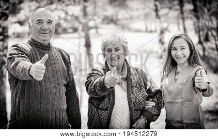 Photo of elderly couple and young caregiver showing thumbs up