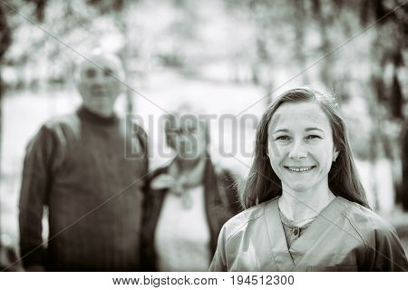 Black and white photo of happy elderly couple and young caregiver