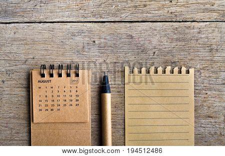 August. Calendar sheet. Two thousand seventeen year calendar pen and list of paper on wooden background.