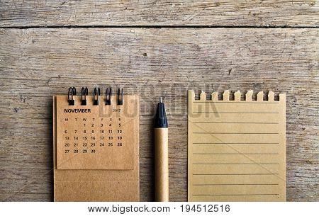 November. Calendar sheet. Two thousand seventeen year calendar pen and list of paper on wooden background.