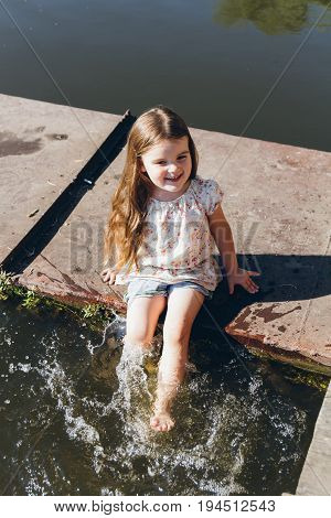 Little Girl Dipping Feet In The Water And Laughing