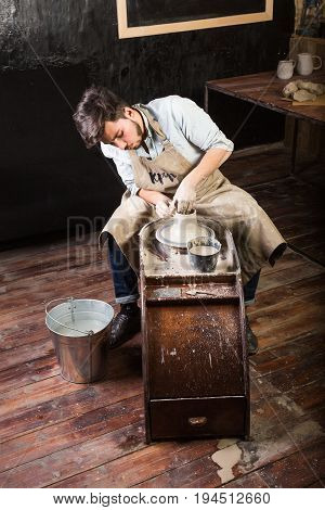 pottery, workshop, ceramics art concept - man's hands works with potter's wheel and clay, young brunette male sculpt cup with fingers and sponge, near master is bucket of water on wooden floor