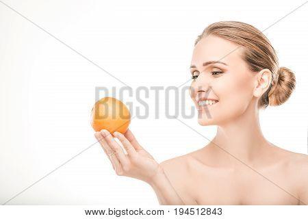Mature female beauty health care studiio portrait holding orange