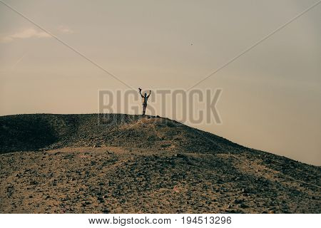 Man with camera and winner gesture on desert hill top with rocky sand surface on grey sky. Barchans dunes and arid landscape. Achievement and success. Hobby. Active leisure. Travelling and wanderlust