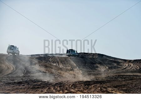 Cars Racing Through Sand Hills In Desert On Blue Sky