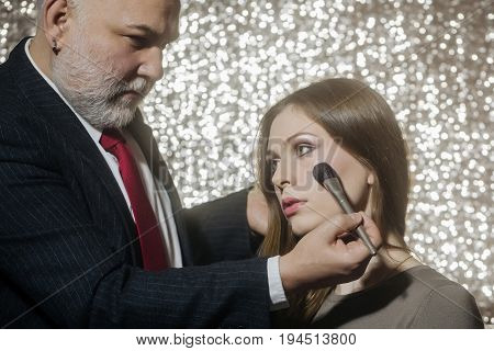 professional makeup artist working with beautiful young woman skincare and cosmetics fashion victim