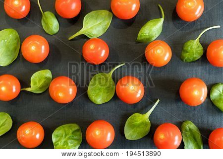 Seamless Pattern With Cherry Tomatoes And Spinach. Abstract Background. Tomato On The Black Backgrou