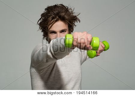 workout of man with barbell or dumbbell has disheveled and uncombed long hair and beard on face in white underwear on grey background morning exercise and wake up barbershop sport