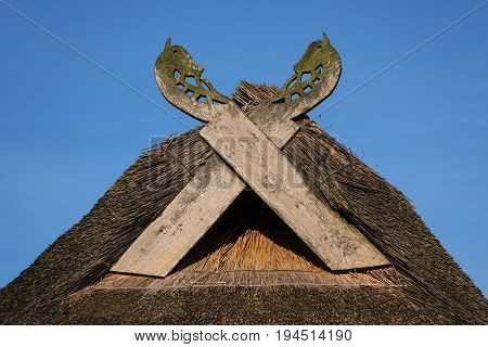Wooden gabled boards in the form of horse heads on a thatched roof against a blue sky on a sunny day typical of traditional houses in northern Germany