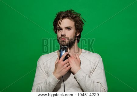 man shaving with electric razor or shaver trimmer with long hair and beard on face in white underwear on green background morning and everyday life barbershop and fashion