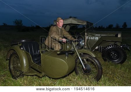 Festival of military history of Russia of XX century . Togliatti, July 7, 2017. Red Army soldier on a motorcycle. Night, artificial light.
