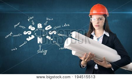 Woman In Orange Helmet Near Wall With Blueprints And Business Idea Sketch Drawn On It. Concept Of A