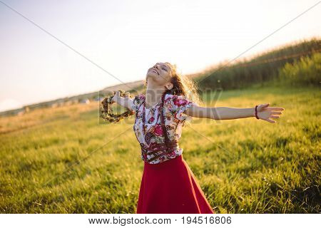 Girl enjoying nature on the field . The girl is joyful spinning with a wreath of flowers in her hands. Free Happy Woman