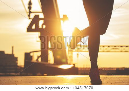 Evening Jogging. Closeup Silhouette Of Young Sporty Woman Jogging On The Bridge During Evening Sunse