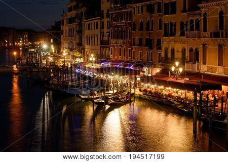 Grand Canal with embankment at night in Venice, Italy. Grand Canal is one of the major water-traffic corridors and tourist attraction in Venice.