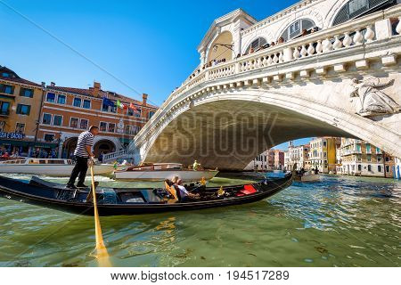 Venice, Italy - May 19, 2017: Gondolier directs the gondola with tourists to the Rialto Bridge on the Grand Canal. The gondola is a traditional romantic transport in Venice.