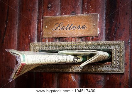 PERUGIA, ITALY. October 26, 2013: Mailbox newspaper inserted into wood doorway, old building house in the city center of Perugia in Italy.