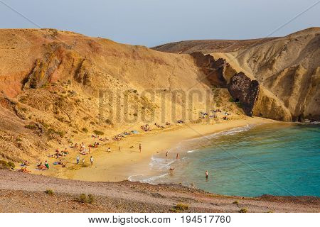 Lanzarote, Playa Blanca, March 31, 2017:group Of People Relaxing On Papagayo Beach On The Island Of