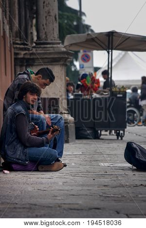 PERUGIA, ITALY. October 26, 2013: Two boys, street performers, theyre playing and singing in the historic center of Perugia (Tuscany, Italy). They are sitting on the ground.