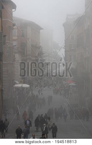 PERUGIA, ITALY. October 26, 2013: The ancient city of Perugia (Tuscany, Italy) with the mist of the morning. Atmosphere and colors that evoke an ancient history. Numerous people walking.