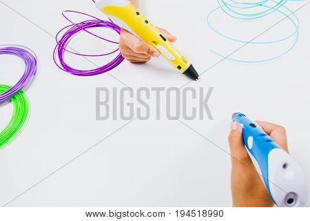 Kids hands holding blue and yellow 3d printing pens with filaments on white background. Top view
