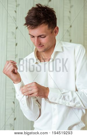 Portrait of a man fastening a cuff before getting married
