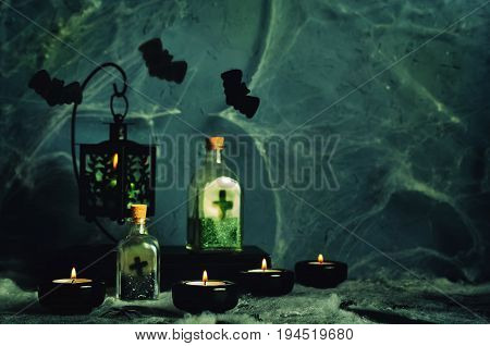Halloween horror background with a spider's web, candles, potions and bats