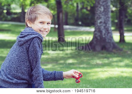 Child playing with spinner outdoors in city park