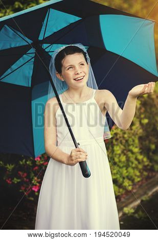 Young girl in communion dress under an umbrella